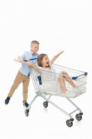 brother riding sister in shopping cart