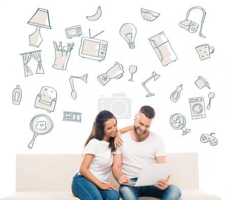 Photo for Young attractive couple using laptop, cartoon house things above heads, isolated on white - Royalty Free Image