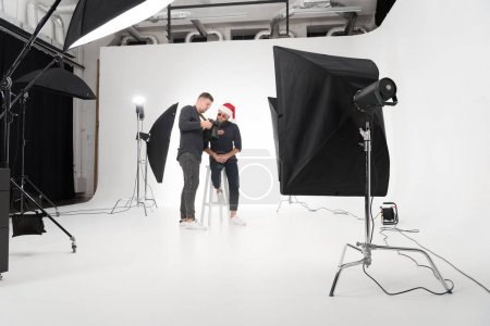 Photo for Young photographer working in studio with model in santa claus hat - Royalty Free Image