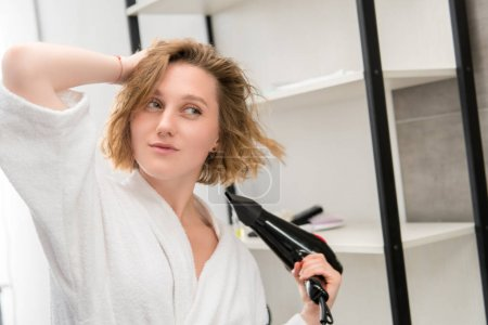 Photo for Beautiful young woman in bathrobe drying hair in bathroom - Royalty Free Image