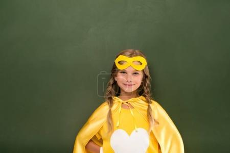 superhero girl next to green chalkboard