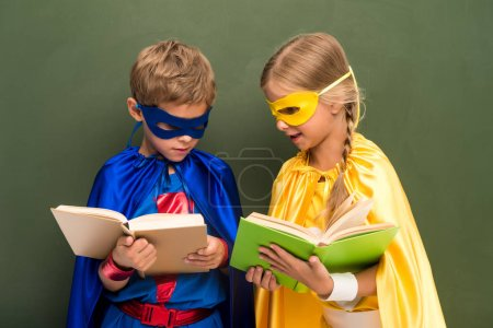 pupils in superhero costumes with books