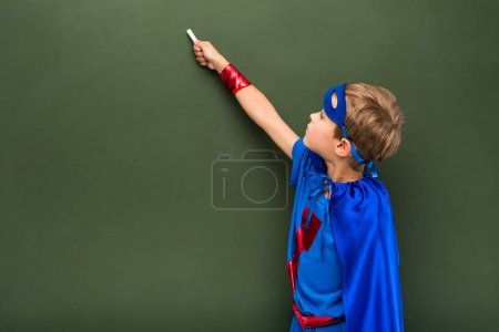 Photo for Schoolchild in blue superhero costume writing on chalkboard - Royalty Free Image