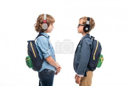 schoolboys with backpacks and headphones
