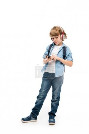 Photo for Adorable schoolboy using smartphone and headphones, isolated on white - Royalty Free Image
