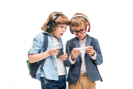excited schoolboys using smartphones