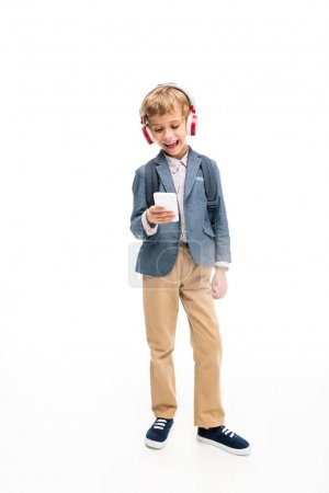 schoolboy using headphones and smartphone