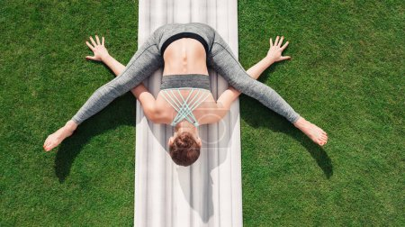 Photo for Overhead view of woman practicing tortoise yoga pose on yoga mat - Royalty Free Image