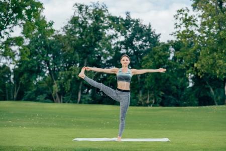 Photo pour Femme sportive pratiquant le yoga étendu main à gros orteil pose dans le parc - image libre de droit