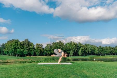 Photo for Athletic young woman practicing yoga crow pose on yoga mat in park - Royalty Free Image