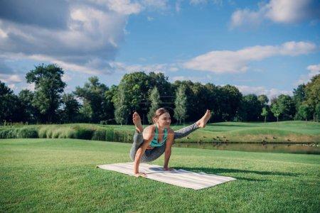 Photo pour Ajustement femme caucasienne en vêtements de sport effectuant yoga luciole pose à la campagne - image libre de droit