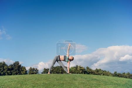 Photo pour Jeune femme effectuant yoga triangle pose tout en exerçant la pelouse de l'om vert - image libre de droit