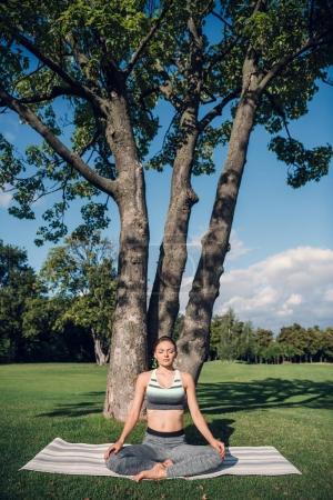 Photo pour Femme caucasienne pratiquant la pose de lotus tout en méditant dans le parc - image libre de droit