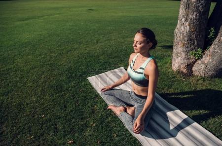 Photo pour Vue latérale du lotus pratiquant détendue femme caucasien posent alors qu'il méditait dans le parc - image libre de droit