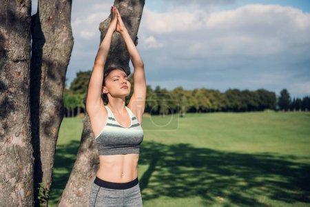 Photo pour Portrait de jeune femme les yeux fermés pratiquant la pose d'arbre de yoga dans le parc - image libre de droit