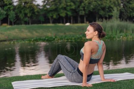 Photo pour Vue latérale de la jeune femme caucasienne se reposant au lac dans le parc - image libre de droit