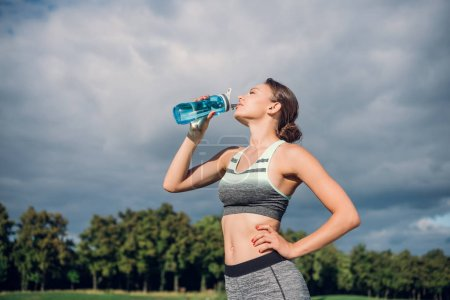 Photo for Portrait of young woman in sportswear drinking water from bottle - Royalty Free Image