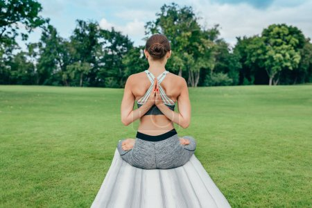 woman meditating on green lawn