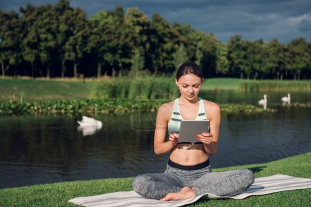 Woman practicing yoga with tablet
