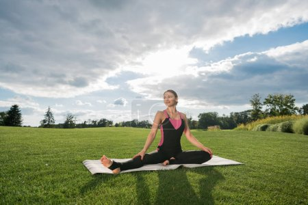 Photo for Smiling woman performing half upright seated angle yoga pose on green lawn in park - Royalty Free Image