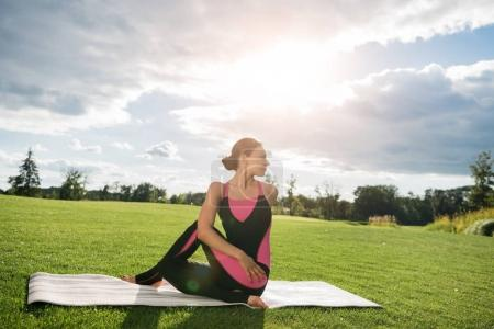 woman sitting in yoga pose in park