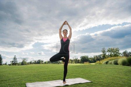 Photo pour Jeune femme pratiquant yoga arbre pose sur tapis de yoga dans le parc - image libre de droit