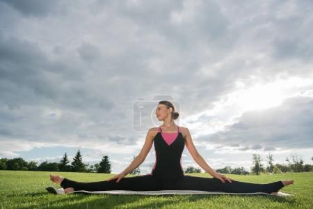 Photo for Smiling woman practicing wide angle seated forward bend yoga pose at countryside - Royalty Free Image