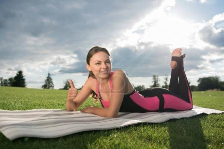 Photo for Smiling woman showing thumb up while resting on yoga mat in park - Royalty Free Image