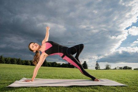 Photo pour Vue latérale de la jeune femme debout dans la pose de yoga chose sauvage sur tapis de yoga dans le parc - image libre de droit