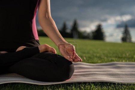 Photo pour Vue partielle d'une femme pratiquant la pose de lotus tout en méditant dans le parc - image libre de droit