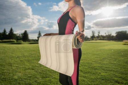 Photo for Cropped shot of woman in sportswear holding yoga mat in park - Royalty Free Image