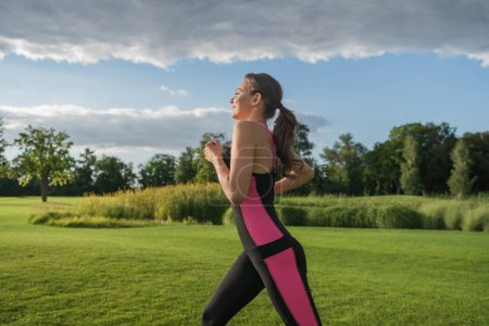 Photo for Side view of smiling sporty woman jogging in park - Royalty Free Image