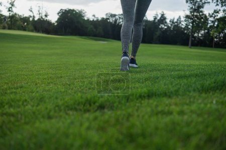 woman running on green lawn