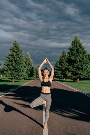Photo for Young woman practicing yoga tree pose on road in park - Royalty Free Image
