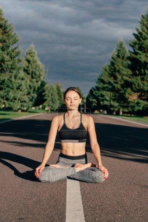 Photo pour Femme caucasienne pratiquant la pose de lotus tout en méditant sur la route dans le parc - image libre de droit