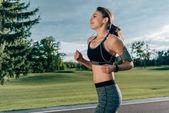 sportive running woman in earphones