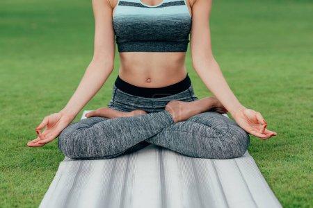 Photo pour Plan recadré de femme effectuant la pose de lotus tout en méditant sur la pelouse verte - image libre de droit
