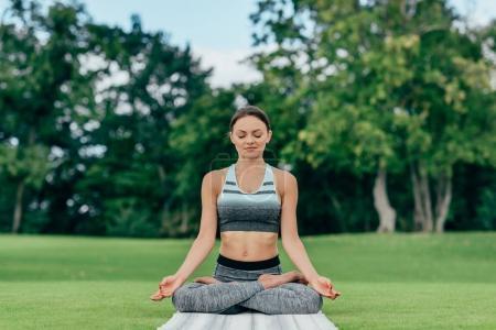 Photo pour Jeune femme exécutant lotus pose tout en méditant sur l'herbe verte dans le parc - image libre de droit