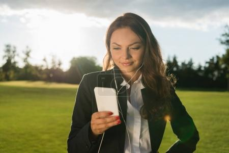 Photo for Portrait of businesswoman in earphones using smartphone on green lawn - Royalty Free Image