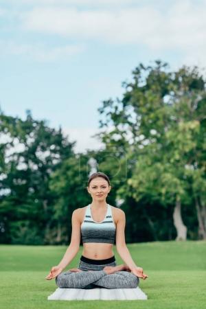 Photo pour Jeune femme effectuant la pose de lotus tout en méditant sur l'herbe verte dans le parc - image libre de droit