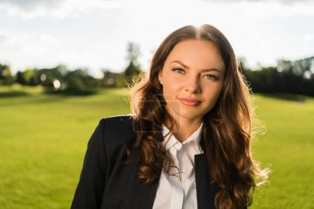 Photo for Portrait of beautiful businesswoman in suit looking at camera in park - Royalty Free Image