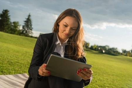 Businesswoman with tablet on green lawn