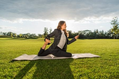Photo for Businesswoman in suit performing King Pigeon Posture yoga pose with tablet - Royalty Free Image