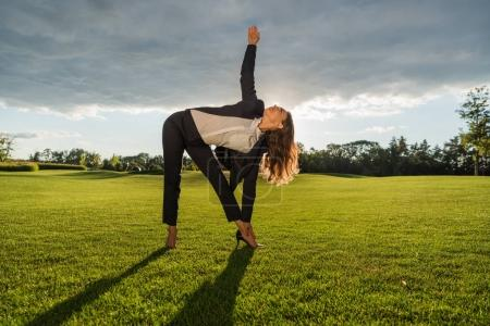 businesswoman standing in yoga pose