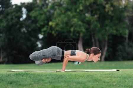 Photo pour Jeune femme sportive pratiquant la pose de corbeau de yoga sur le tapis de yoga dans le parc - image libre de droit