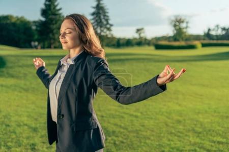 Photo pour Portrait de femme d'affaires souriant méditant dans le parc - image libre de droit