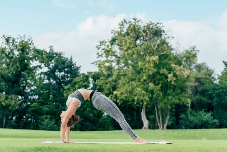 Photo for Side view of woman in sportswear practicing yoga wheel pose (upward bow pose) in park - Royalty Free Image