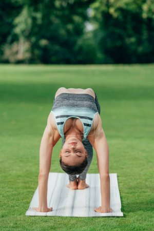 Photo for Woman in sportswear practicing yoga wheel pose (upward bow pose) in park - Royalty Free Image