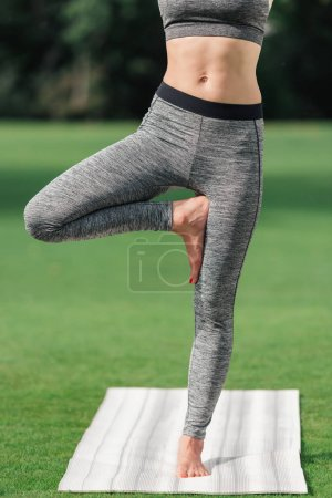 woman practicing yoga tree pose