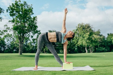Photo pour Vue latérale de la jeune femme pratiquant la pose de triangle de yoga à la campagne - image libre de droit